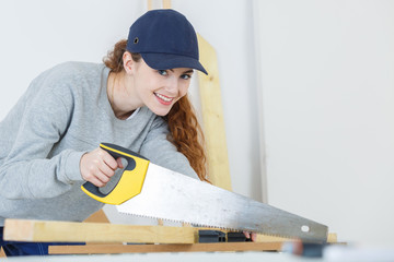woman carpenter sawing lumber