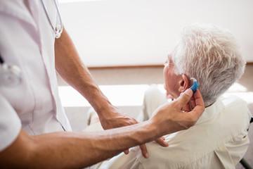 Nurse giving hearing device to a senior man
