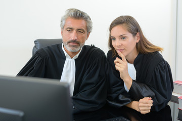 Male and female magistrates looking at computer