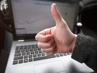 man shows thumbs up on laptop background with graph of sales growth.business man working while being in the car. .