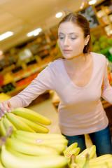 Lady in supermarket choosing bananas