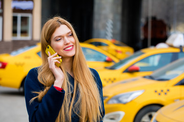 A young girl calls a taxi by phone.