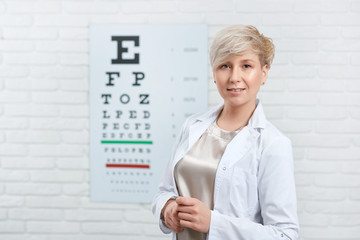 Portrait of skilled ophthalmologist staying in front of visual inspection table, hanging on white wall in medical laboratory. Expirienced doctor helping peple to improve their eye health and vision.
