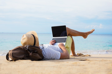 Relaxed man with laptop on the beach Fotomurales