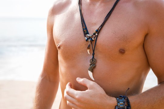Shirtless man with necklaces