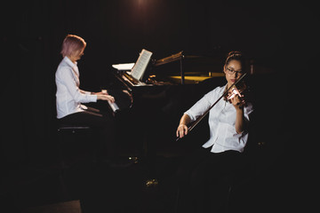 Two female students playing violin and piano