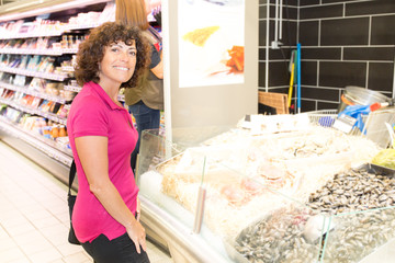 woman choosing products in fish counter supermarket