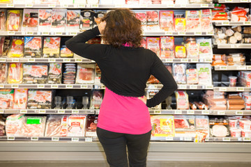 Young woman shopping in the supermarket can not choose or there is not the product she wants
