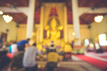 Abstract blur image of People go to make merit in the temple on Buddhist religious significance with bokeh for background usage. (vintage tone)