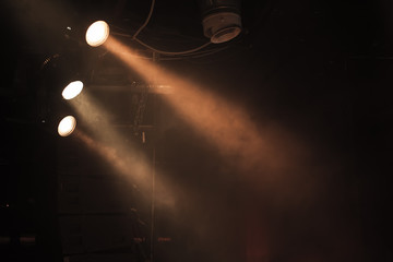 Three spot lights with strong beams in smoke