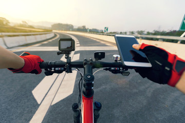 Cyclist using smartphone for navigation when riding mountain bike on highway