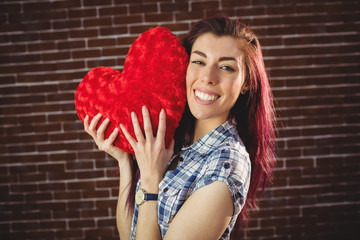 Woman holding a red heart plush