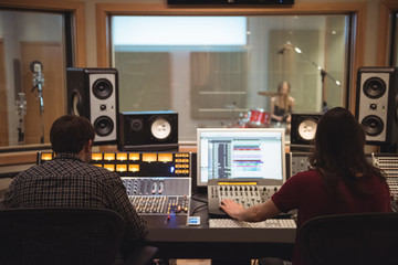 Audio engineers using sound mixer in recording studio