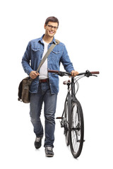 Young man with a bicycle walking towards the camera