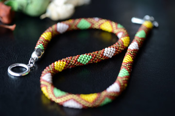 Ethnic style beaded necklace on a dark background close up