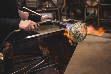 Glassblower giving final touch to a piece of glass with glassblowing torch