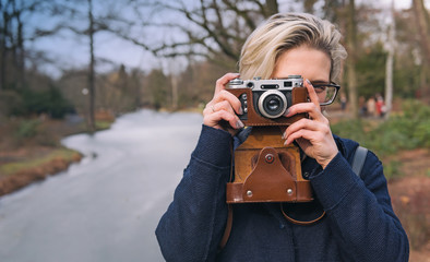 Young blonde woman holding retro photo camera and taking photo in the forest. River on background. Nature concept. Outdoor portrait