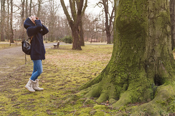 Young blonde woman in hoodie holding retro photo camera and taking photo in the forest. Autumn nature concept.