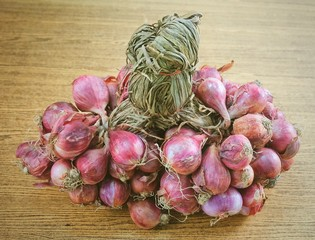 Bunch of Fresh Red Onions on Wooden Table