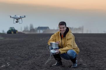 Farmer navigating drone above farmland