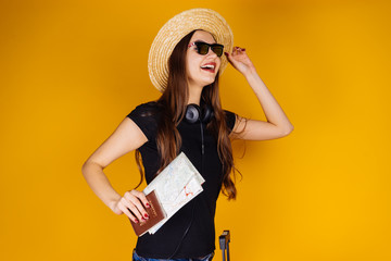 happy young girl in a hat and sunglasses going on vacation, holding a passport and tickets for a plane