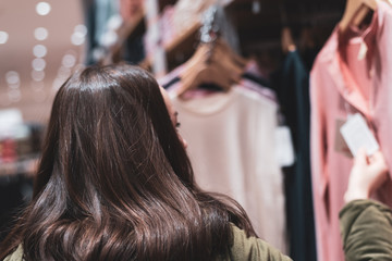 A young brunette chooses spring clothes. shopping concept