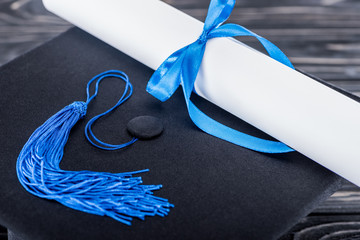 High school concept with diploma and graduation cap on wooden table