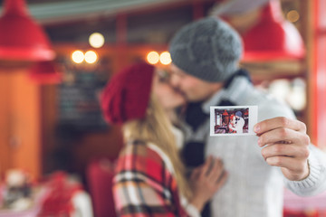 Kissing young couple with a photo