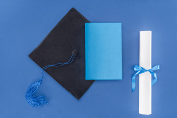High school concept with diploma and graduation cap isolated on blue