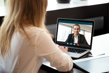 Businesswoman making video call to business partner using laptop. Close-up rear view of young woman having discussion with corporate client. Remote job interview, consultation, human resources  concep