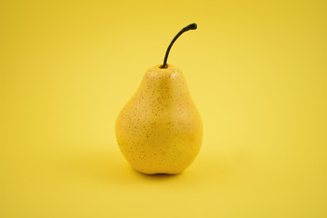 Pear decoration stock images. Yellow pear on a yellow background. Pear home decor. Yellow decorative pear