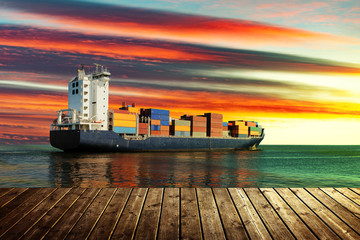 View from wooden pier with container ship on sea during sunset.