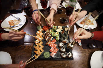 Printed kitchen splashbacks Sushi bar A set of sushi rolls on a table in a restaurant. A party of friends eating sushi rolls using bamboo sticks.