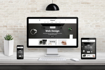 Responsive web site template design presentation on computer, smart phone and tablet display. Studio desk with brick wall in background. Wall mural