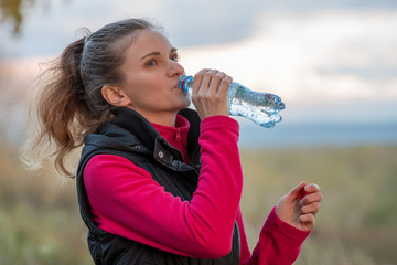 Beautiful woman drinks clean water after jogging and sport in autumn