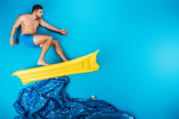 handsome young man in shorts surfing on inflatable mattress on imagine sea on blue Wall mural