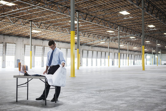 Businessman going over plans for new warehouse interior in front of loading dock doors