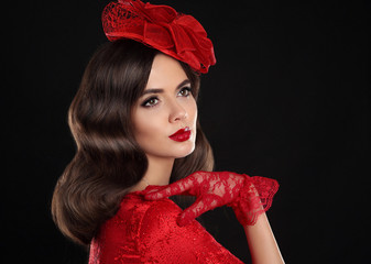Retro Woman Portrait. Vintage Style Girl Wearing red fashion Hat and Gloves, wavy Hairstyle and Makeup. Romantic lady isolated on black studio background