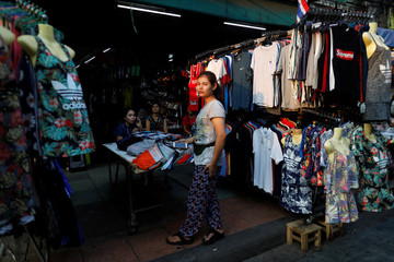 Women sell clothes on a street side in Bangkok