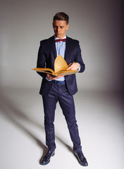 a man, a guy in a blue suit, stands and reads an old book, the concept of knowledge, study, science, business, everything new, it's a well-forgotten old