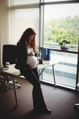Pregnant businesswoman touching her belly