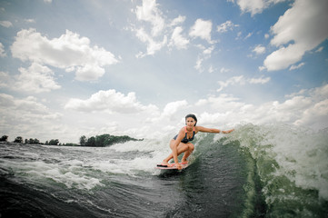 Beautiful woman wakesurfing on the board against the sky