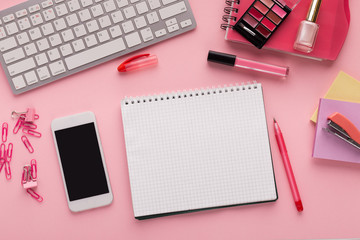 Working space with notepad and smartphone on pink background