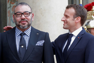 French President Emmanuel Macron welcomes Morocco's King Mohammed VI as he arrives for a meeting at the Elysee Palace in Paris