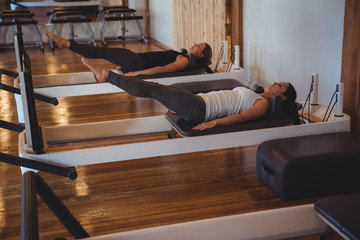 Women practicing pilates on reformer