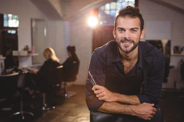 Smiling male hairdresser leaning on chair in salon