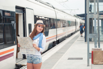 Traveler girl waits train on railway platform with a map and she enjoys the upcoming trip. Travel concept.