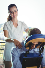Female physiotherapist giving back massage to a male patient