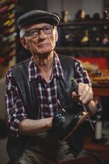 Portrait of shoemaker repairing a shoe
