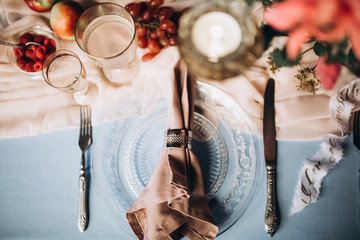 close-up of a glass plate with a napkin with vintage instruments on a festive table served with a blue tablecloth vintage glasses and flowers with candles on a wooden wall background